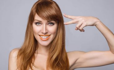 Hairdresser cutting woman bangs hair in shop. Beauty salon. Hand with two fingers up in the peace or victory symbol the sign for V. Hair. Brunette girl with long and shiny wavy hair.; Shutterstock ID 550746529; Job: RD